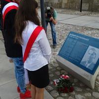 Natalia Szkodzińska, Rafał Stępniewski i Klaudia Swoboda z Zespołu Szkół nr 42 im. Jana Karskiego składają kwiaty pod tablicą Patrona bulwaru